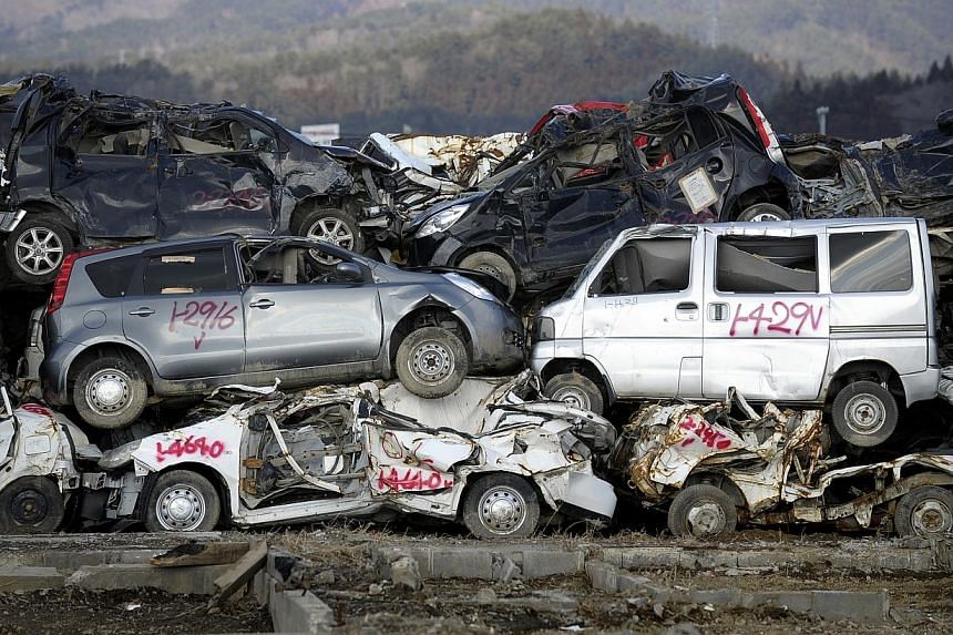 ORDERED CHAOS: Wrecked cars lie neatly stacked atop one another along a street in Kensennuma, Miyagi prefecture, 11 months after the area was devastated by a tsunami. Huge efforts are being made to restore order amid the chaos. Debris has been sorted