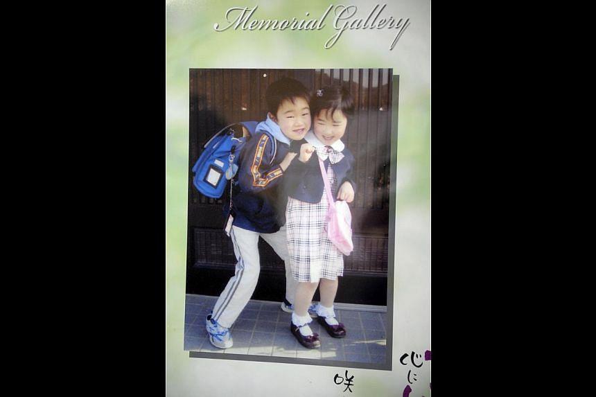 IN MEMORIAM: Mrs Masako Karino lost both her children, son Tatsuya, 11, and daughter Misaki, 8, when the tsunami swept through the Okawa Elementary School last year. She has a shrine to their memory in her house. Nestled among the numerous photos tha