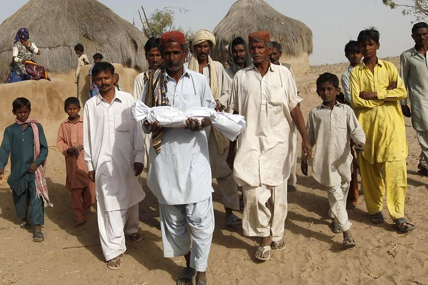 Family members and villagers carry the body of two-month-old Mangal, who died of infection, for his burial in a drought-stricken area of Kaposar village of Mithi, in the Sindh province, March 11, 2014.Mangal succumbed to pneumonia on Tuesday in