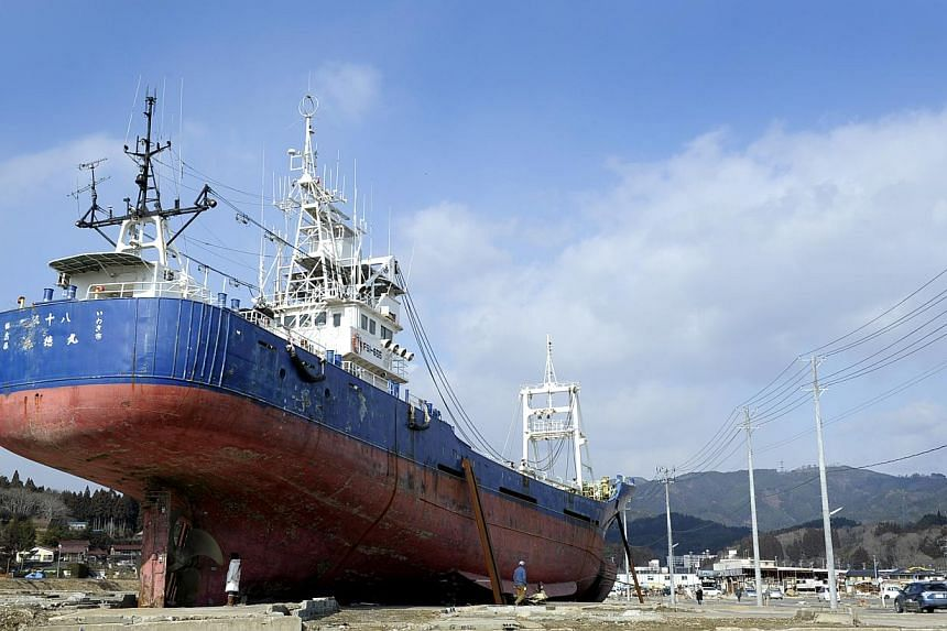 """STARK REMINDER: A car passing by a huge """"landmark"""" in Kensennuma city, Miyagi prefecture, last month. The 60m-long fishing trawler, the Kyotoku-maru, was docked in the city's harbour on March 11 last year before being caught up in the huge wave"""