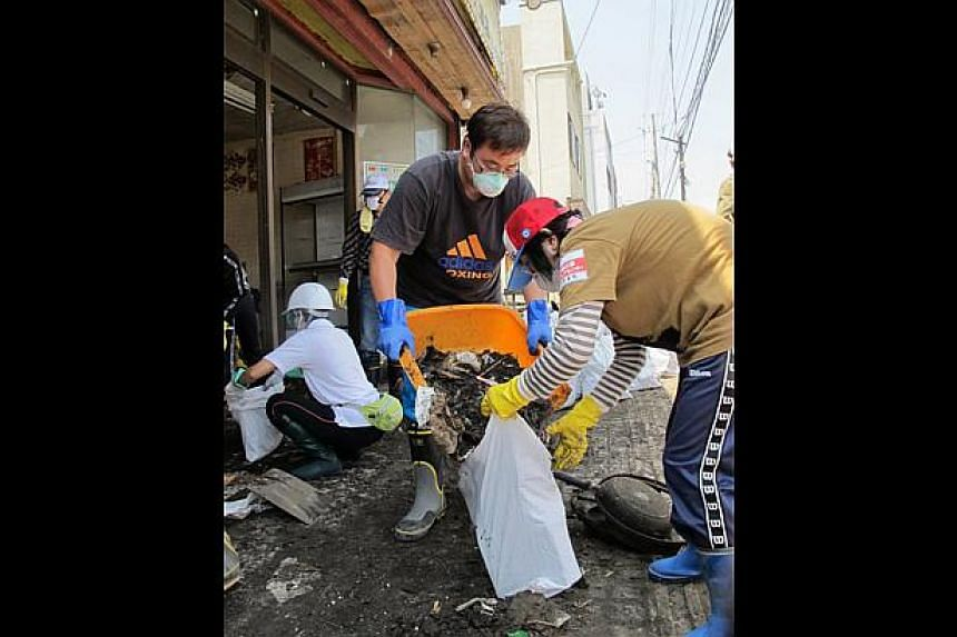 VOLUNTEERING: Mr Lai (in grey shirt) clearing debris from a shop in Kamaishi city, Iwate prefecture, last July. -- FILE PHOTO: LAI YING LOONG
