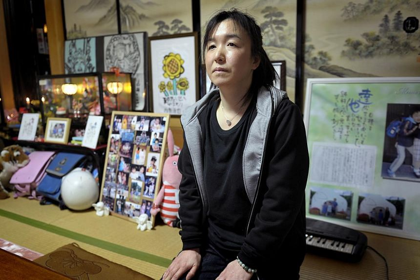 IN MEMORIAM: Mrs Masako Karino lost both her children, son Tatsuya, 11, and daughter Misaki, 8, when the tsunami swept through the Okawa Elementary School last year. She has a shrine to their memory in her house. Nestled among the numerous photos tha