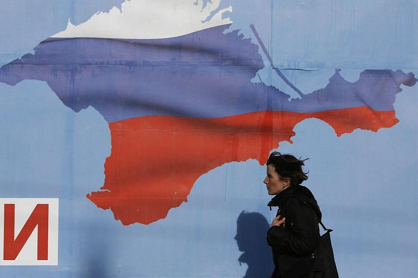 A woman walks by a poster in the Crimean port city of Sevastopol on March 10, 2014.Pro-Moscow lawmakers in Crimea voted for independence from Ukraine on Tuesday in a precursor to a referendum this weekend for the region to become part of Russia