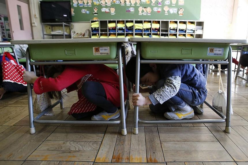 Students taking shelter in their classroom during an earthquake simulation exercise at an elementary school in Tokyo on March 11, 2014. -- PHOTO: REUTERS