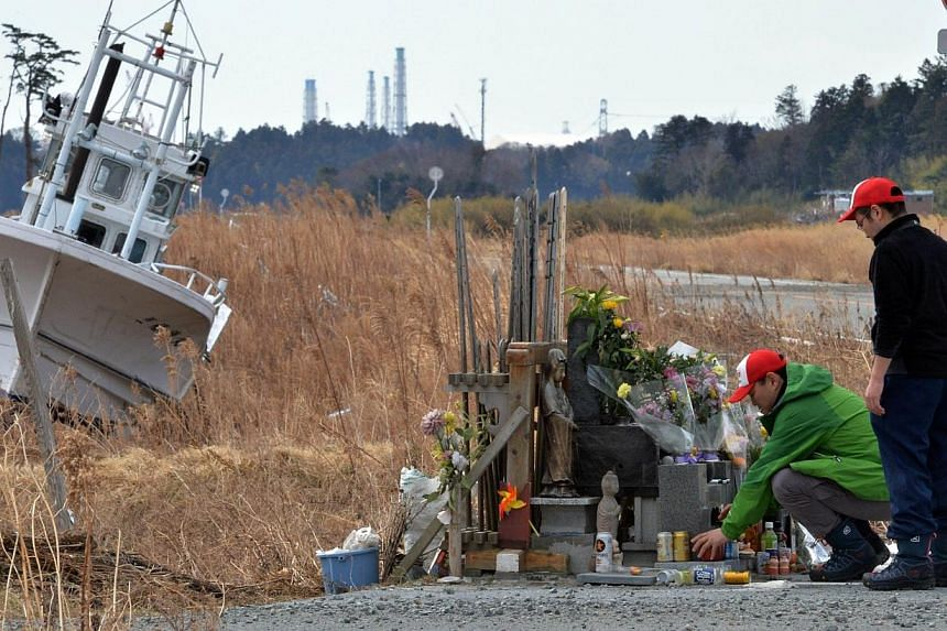 Two men offering prayers at Namie, near the striken Fukushima nuclear plant in Fukushima prefecture on March 11, 2014, three years after the disastrous earthquake and tsunami which hit northern Japan. -- PHOTO: AFP