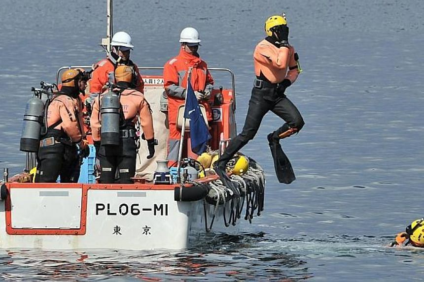 Divers of a Japanese Coast Guard marine rescue unit jumping into the waters in the hope of finding missing people at Tsukahama coastal area in Onagawa, Miyagi prefecture on March 10, 2014, a day before the third anniversary of March 11, 2011 earthqua