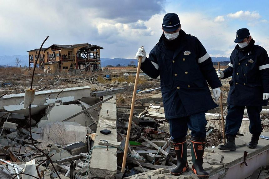 Police officers combing Namie for any sign of missing people on March 10, 2014, three years after the massive Japan earthquake and tsunami. -- PHOTO: AFP