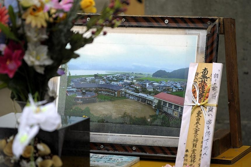 ON SITE: Okawa Elementary School before (in a framed photo) the tsunami swept in and killed 74 people. - ST FILE PHOTO: JOYCE FANG