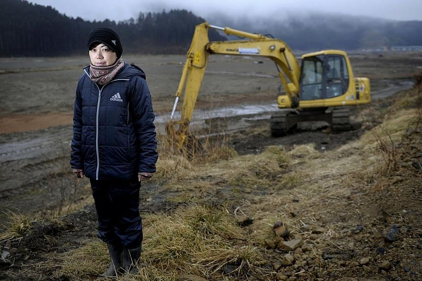 DETERMINED: Mrs Naomi Hiratsuka, 37, learnt to operate an excavator while searching for her 12-year-old daughter Koharu. Her daughter's body was found five months after the tsunami swept through Okawa Elementary School in March last year. Mrs Hirat