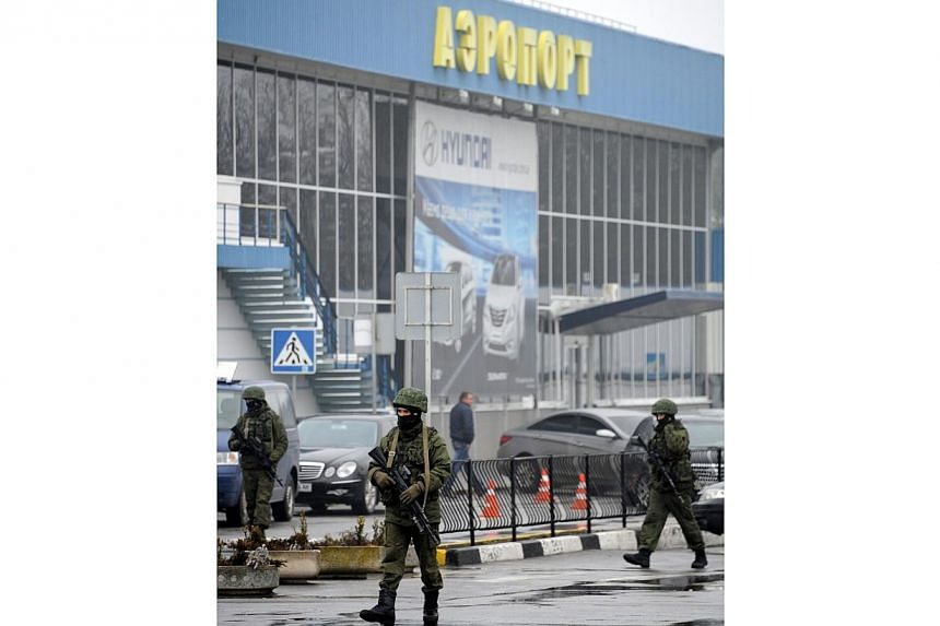 A photo taken on Feb 28, 2014 shows unidentified armed men patrolling outside Simferopol airport.Lawmakers on the flashpoint Crimean peninsula voted on Tuesday, March 11, 2014, for independence from Ukraine ahead of a referendum on joining Russ