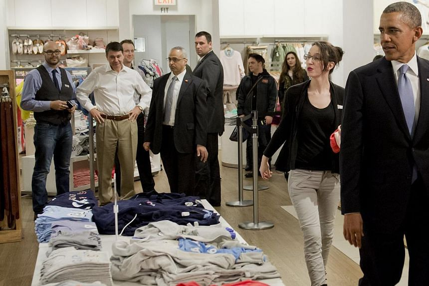 United States President Barack Obama shops for clothing for his family alongside store employee Susan Panariello (left) during a visit to a Gap clothing store in New York City, March 11, 2014. -- PHOTO: AFP