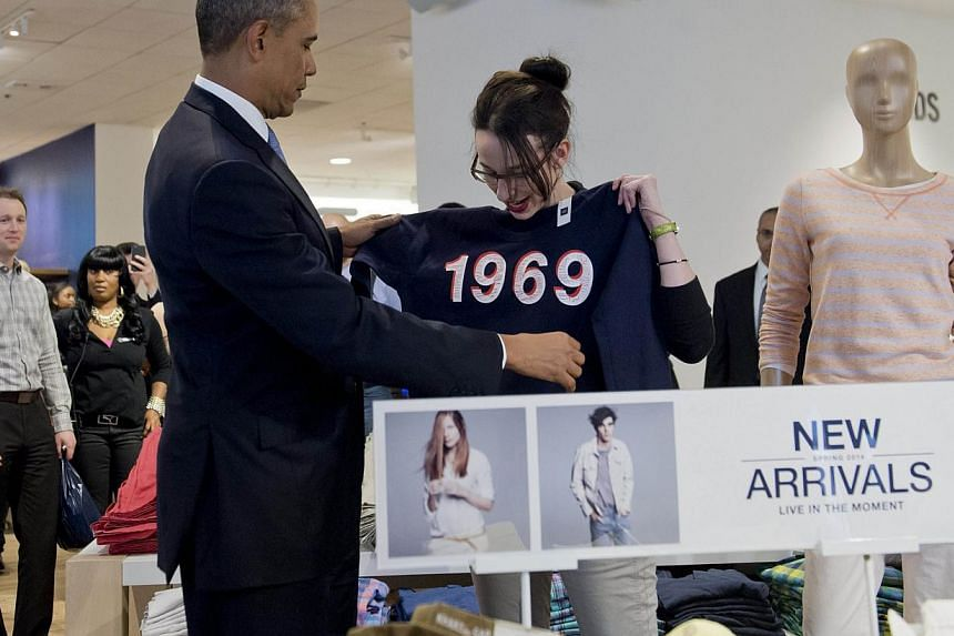 United States President Barack Obama shops for clothing for his family alongside store employee Susan Panariello (right) during a visit to a Gap clothing store in New York City, March 11, 2014. -- PHOTO: AFP
