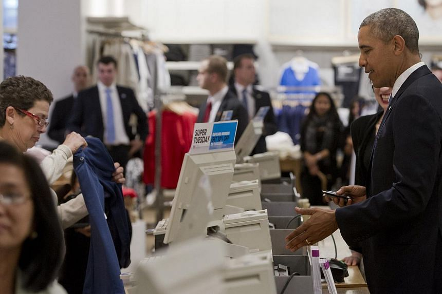 United States President Barack Obama pays for his purchases after shopping for clothing for his family during a visit to a Gap clothing store in New York City on March 11, 2014. -- PHOTO: AFP