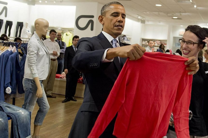 United States President Barack Obama holds up a shirt as he shops for clothing for his family alongside store employee Susan Panariello (right) during a visit to a Gap clothing store in New York City on March 11, 2014. -- PHOTO: AFP