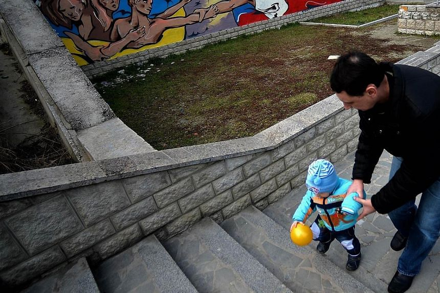 A man and his child walk by a mural depicting Russian president Vladimir Putin giving a hand to Ukranians in Simferopol on March 12, 2014.Hundreds of people have fled Crimea and the situation could deteriorate further as tensions continue to ri