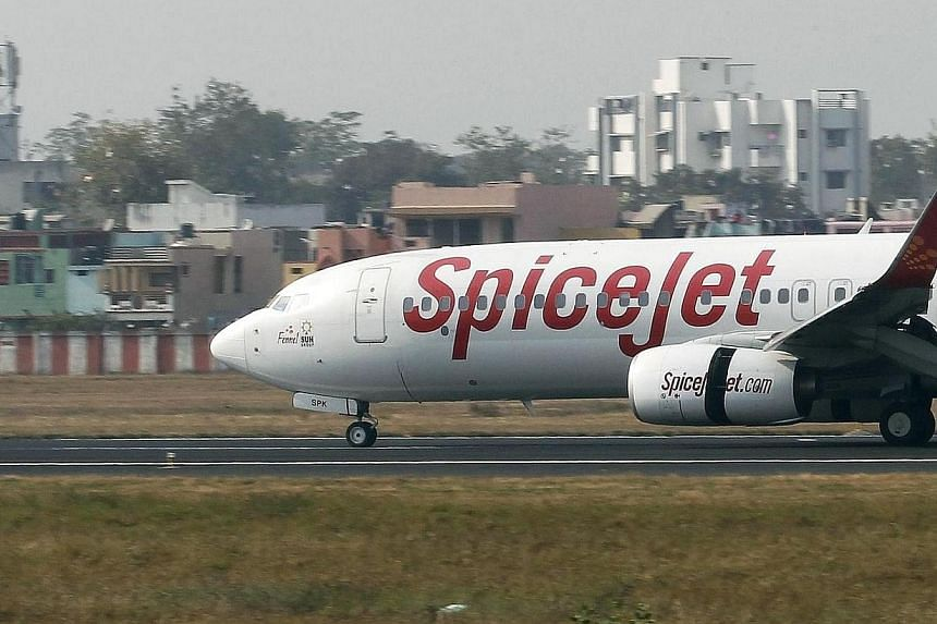 A SpiceJet passenger plane moves on the runway at the Sardar Vallabhbhai Patel international airport in the western Indian city of Ahmedabad January 8, 2014. Indian budget airline SpiceJet Ltd has signed a deal with Boeing Co to buy 42 737 MAX jets i