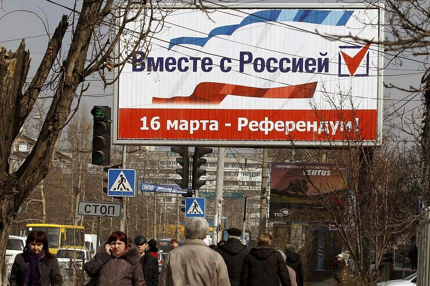 """People walk under a sign that reads, """"Together with Russia. March 16 - referendum"""", in the centre of Simferopol, March 12, 2014. The Group of Seven most developed economies on Wednesday, March 11, 2014, said a Moscow-backed referendum in Crimea on sw"""