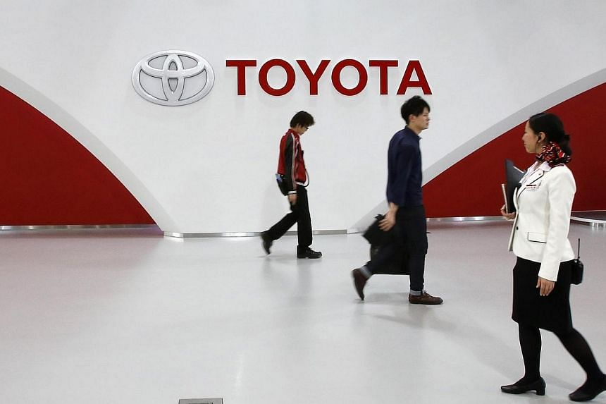 Employees and a customer (centre) walk in front of Toyota Motor's logo at the company's showroom in Tokyo March 12, 2014. Toyota Motor Corp said it will give its Japan-based workers their biggest pay raise in 21 years in the year starting in April, h
