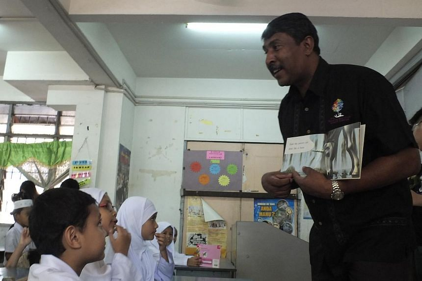 Mr Cheli Nadarajah reading a children's story with a group of eight-year-olds in Sentul, Kuala Lumpur. He and his wife run The Reading Bus Club, a mobile library to encourage children to read English story books amid falling English standards in the