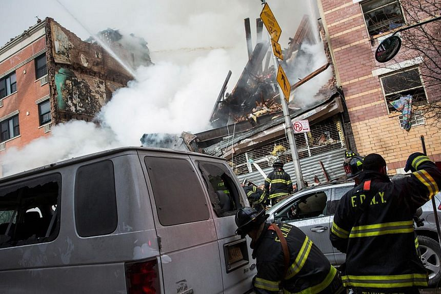 Firefighters from the Fire Department of New York (FDNY) respond to a 5-alarm fire and building collapse at 1646 Park Ave in the Harlem neighborhood of Manhattan March 12, 2014 in New York City. -- PHOTO: AFP