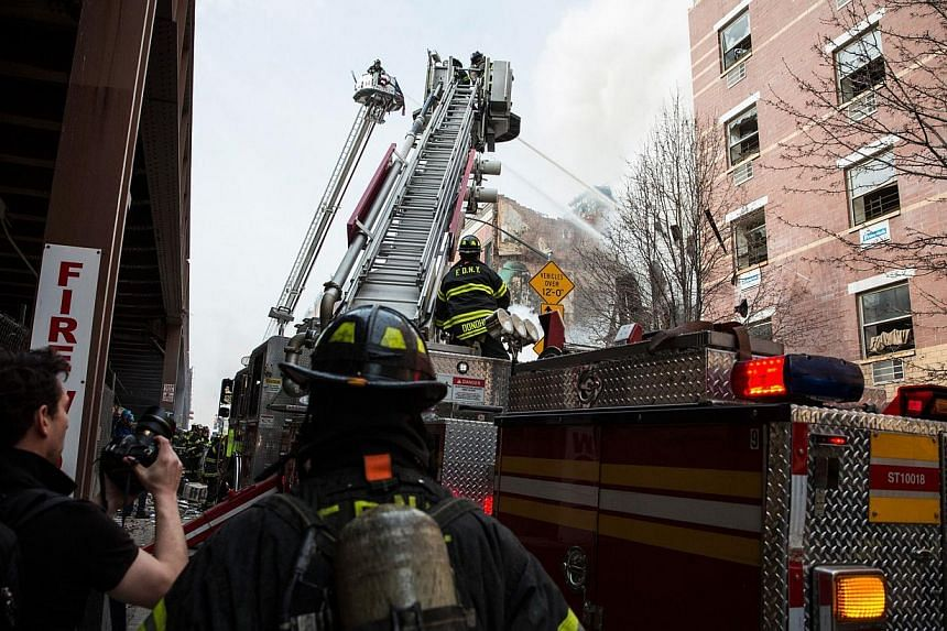 A ladder truck pours water as the Fire Department of New York (FDNY) respond to a 5-alarm fire and building collapse at 1646 Park Ave in the Harlem neighborhood of Manhattan March 12, 2014 in New York City. -- PHOTO: AFP