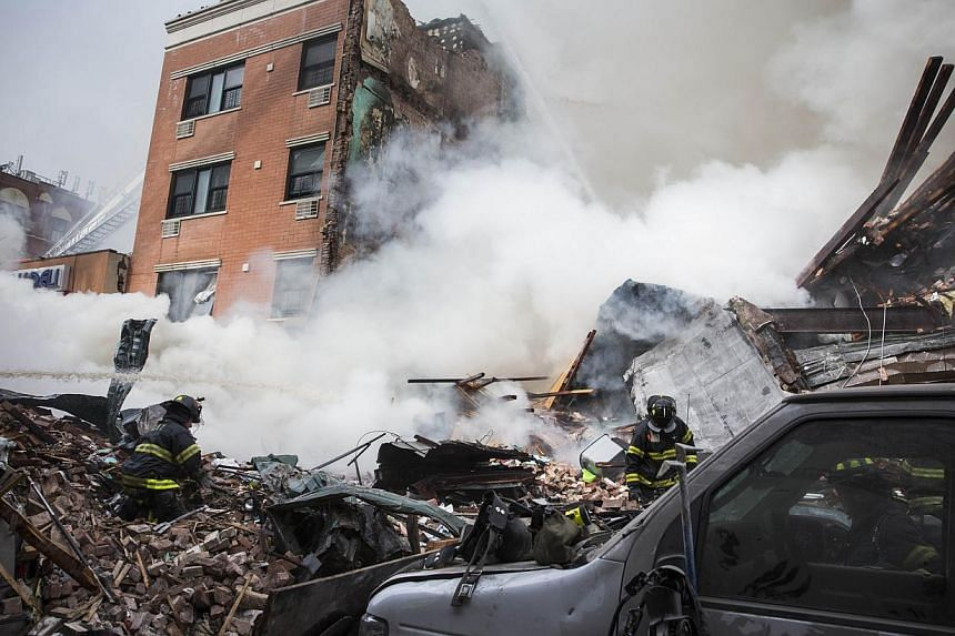 Heavy smoke pours from the debris as the Fire Department of New York (FDNY) responds to a 5-alarm fire and building collapse at 1646 Park Ave in the Harlem neighborhood of Manhattan March 12, 2014 in New York City. -- PHOTO: AFP