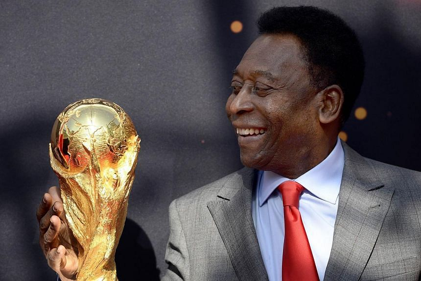 Brazilian football legend Pele looks at the FIFA World Cup trophy during the FIFA World Cup Trophy event on March 9, 2014, outside the Hotel de Ville in Paris. Both SingTel and StarHub pay-TV viewers will get to watch this year's World Cup in Brazil