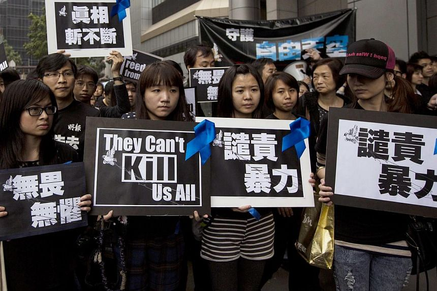 Staff members of Ming Pao newspaper take part in the march against violence on journalists in Hong Kong on March 2, 2014. Two Hong Kong men suspected of attacking former Ming Pao editor Kevin Lau in a brutal cleaver attack last month have been a