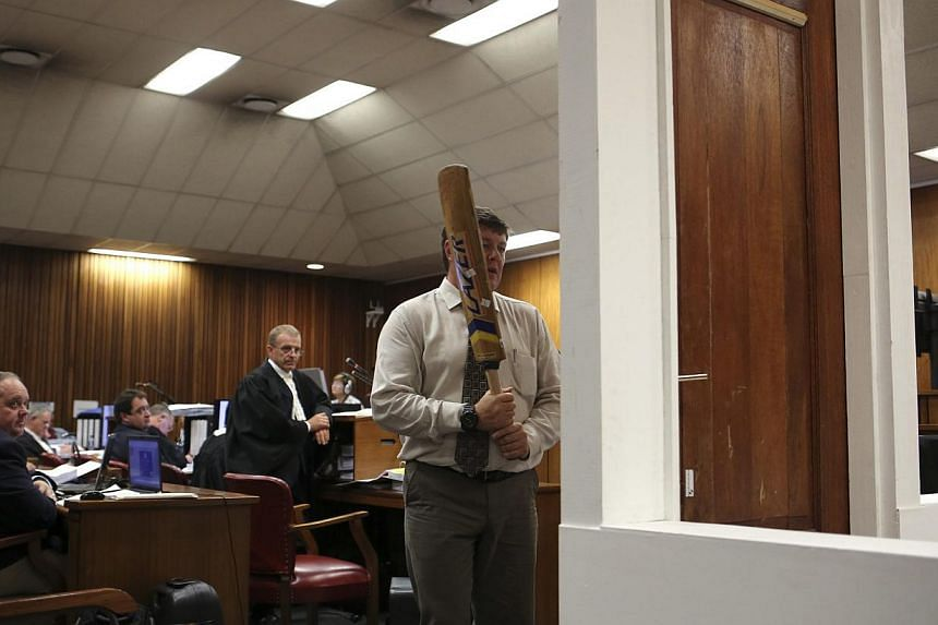 A policeman demonstrates the effect of hitting of a bathroom door with a cricket bat during the trial of South African Paralympic athlete Oscar Pistorius in the North Gauteng High Court in Pretoria, March 12, 2014. A forensics expert on Wednesday sta