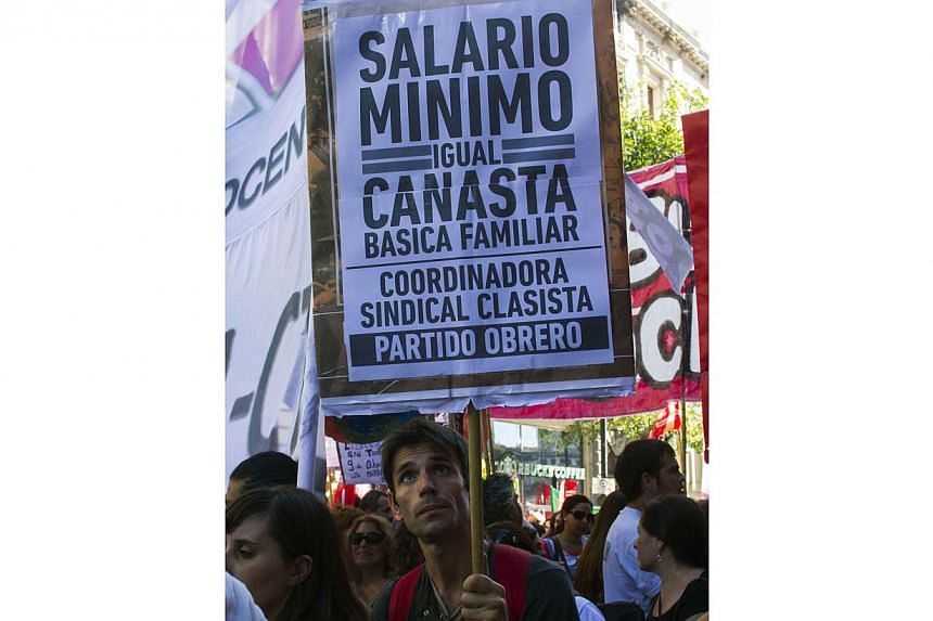 """Protesters take part in a one-day nationwide protest to demand an increase in their monthly wages and a halt in dismissal and suspension of employees in Buenos Aires on March 12, 2014. The placard reads """"Minimum salary equals basic shopping basket""""."""