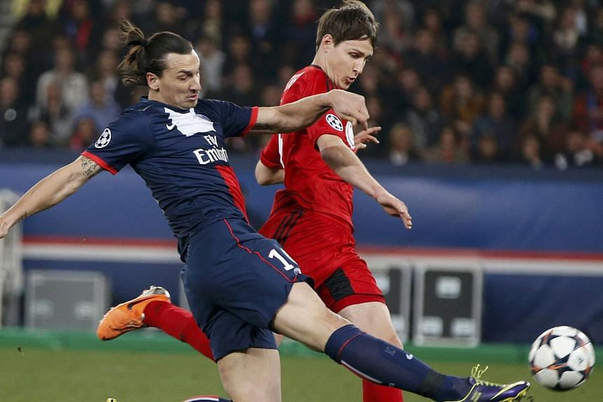 Paris St Germain's Zlatan Ibrahimovic (left) challenges Bayer Leverkusen's Andres Guardado during their Champions League round of 16 second leg soccer match at the Parc des Princes Stadium in Paris on March 12, 2014. -- PHOTO: REUTERS