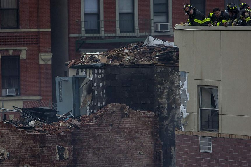 New York City firefighters examine the rubble at an apparent building explosion and collapse in the Harlem section of New York on March 12, 2014. -- PHOTO: REUTERS