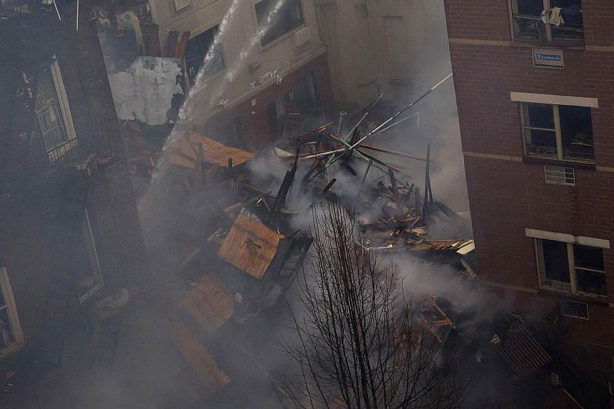 New York City firefighters spray water onto the rubble at an apparent building explosion and collapse in the Harlem section of New York on March 12, 2014. -- PHOTO: REUTERS
