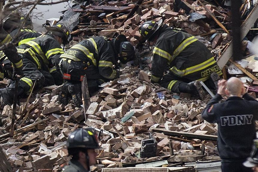 New York City firefighters dig through rubble of a building explosion and collapse in the Harlem section of New York on March 12, 2014. -- PHOTO: REUTERS