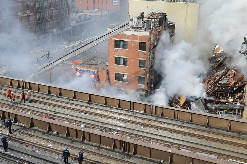 Firefighters try to extinguish a fire as smoke bellows from the site of a building collapse in Harlem, New York in this picture provided by Adnan Islam on March 12, 2014. -- PHOTO: REUTERS