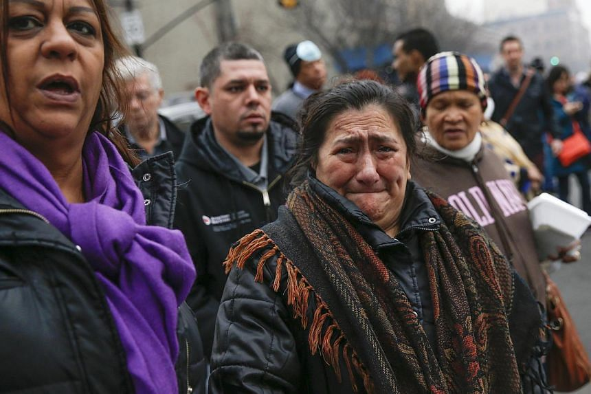 A woman cries as she is brought to the site of a building collapse in Harlem, New York on March 12, 2014. -- PHOTO: REUTERS