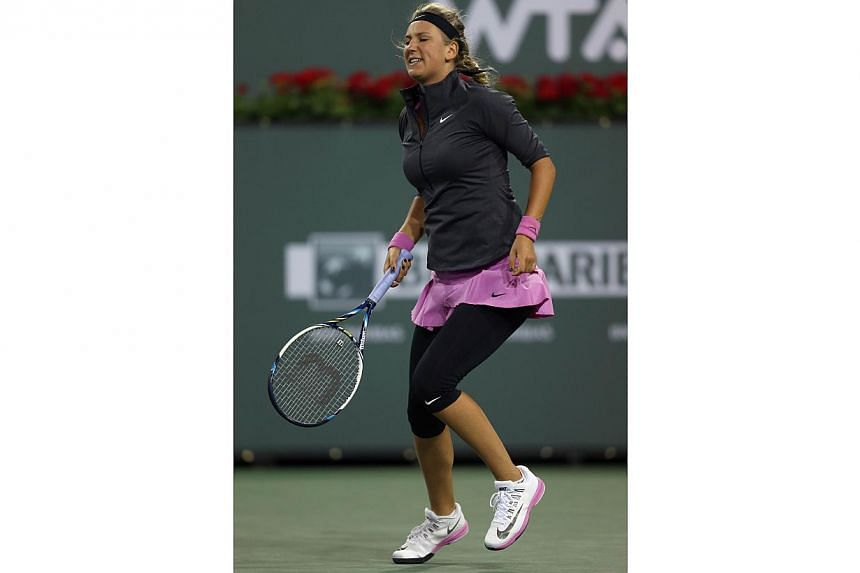 Victoria Azarenka of Belarus favours one leg after returning a shot to Lauren Davis during the BNP Paribas Open at Indian Wells Tennis Garden on March 7, 2014 in Indian Wells, California.Azarenka is nursing a foot injury, one that hindered the
