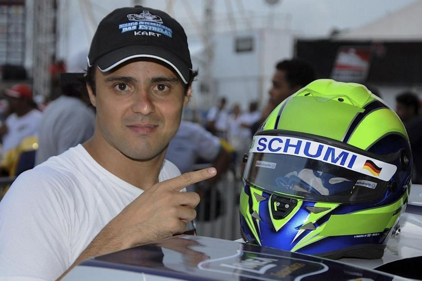 """Former Ferrari Formula One driver Felipe Massa points to his helmet painted with the nickname """"Schumi"""" as a tribute to Michael Schumacher, before competing in a karting race International Challenge of the Stars in Penha on Jan 11, 2014. Massa remains"""