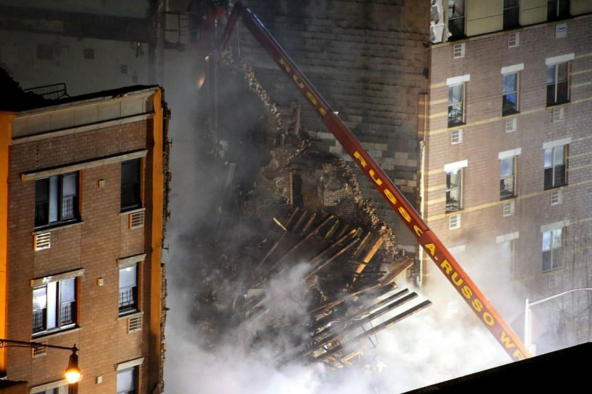New York City firefighters respond to a five-alarm fire and building collapse at 1646 Park Ave in the Harlem neighborhood of Manhattan, on March 12, 2014, in New York City. A major explosion caused by a gas leak flattened two Manhattan apartment buil
