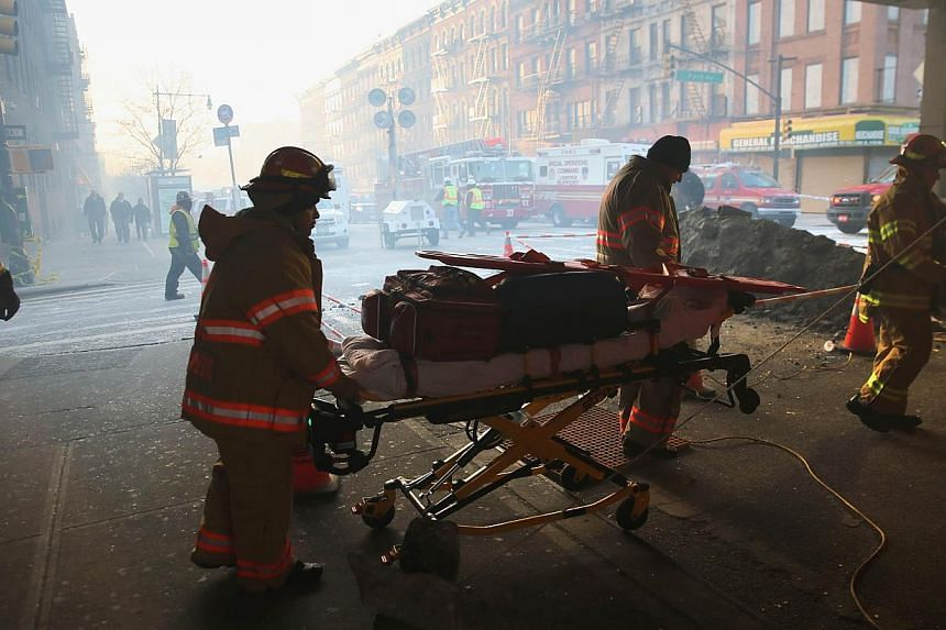 Smoke fills 116th street as a stretcher of paramedic equipment is wheeled near the site of an explosion in East Harlem, on March 13, 2014, in New York City. The death toll from an explosion that collapsed two New York apartment buildings after an app
