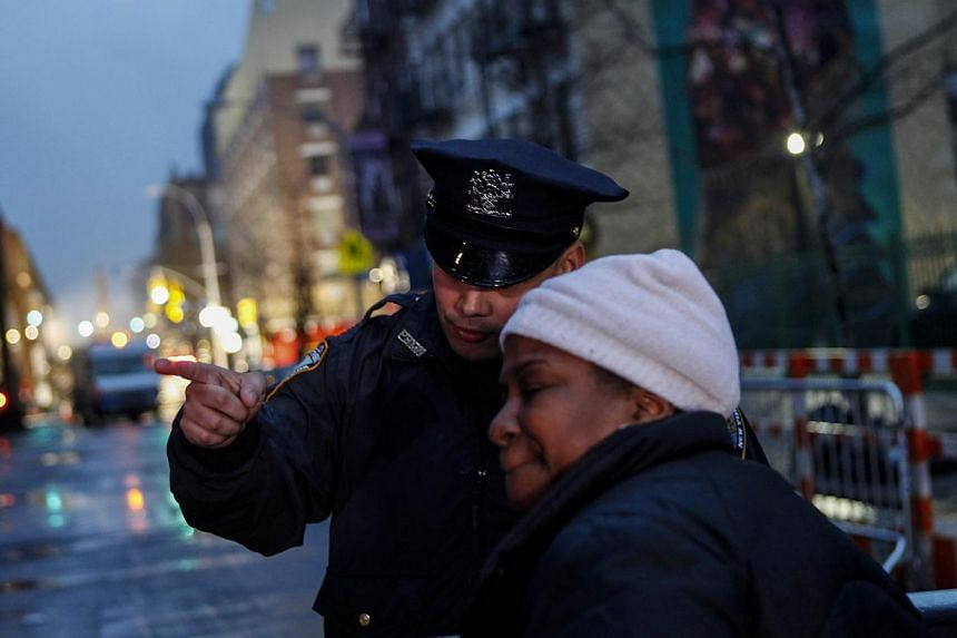 A police officer talks to a resident displaced after a building collapse at 1646 Park Ave in the Harlem neighborhood of Manhattan, on March 12, 2014, in New York City. -- PHOTO: AFP