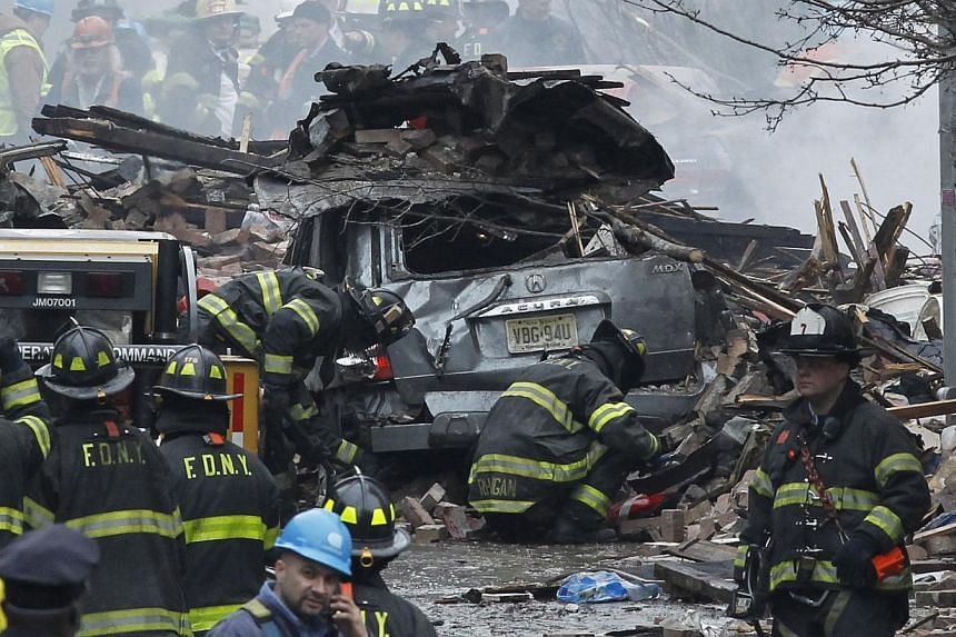Emergency personnel look on as a body is removed from the rubble following a building collapse in the Manhattan borough of New York, on March 12, 2014. -- PHOTO: REUTERS