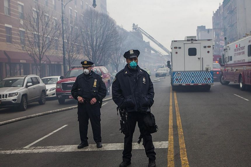 Two police officers a block from the scene of a gas leak explosion that caused two buildings to collapse on Park Avenue and 116th street in the Harlem neighborhood of Manhattan, on March 12, 2014, in New York City. -- PHOTO: AFP