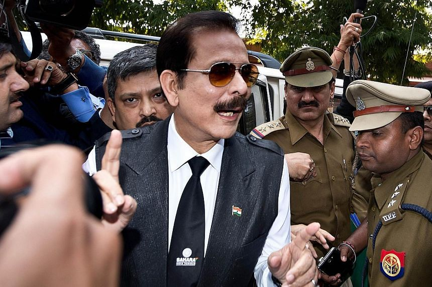 India's Sahara group chairman Subrata Roy (centre) speaks to the media as he arrives at the Supreme Court in New Delhi, on March 4, 2014. India's Supreme Court on Thursday, March 13, 2014, rejected a petition by the head of the unlisted Sahara conglo