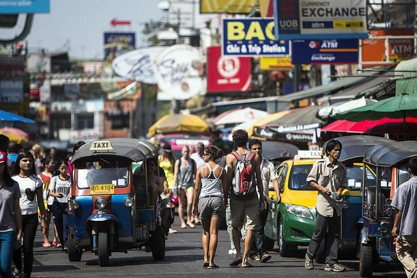 Tourists walk along Khao San Road tourist district in the morning after a shooting incident at an intersection near the street, in central Bangkok on Jan 11, 2014. Khao San Road, crammed with budget tourists from across the world, has long been a bac