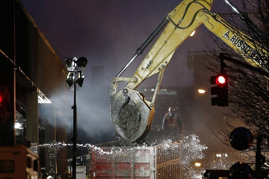 An excavator clears debris at the site of a building explosion in the Harlem section of New York on March 13, 2014. Rescuers scouring the rubble of two Manhattan apartment buildings leveled in a gas explosion found the body of an eighth victim on Thu