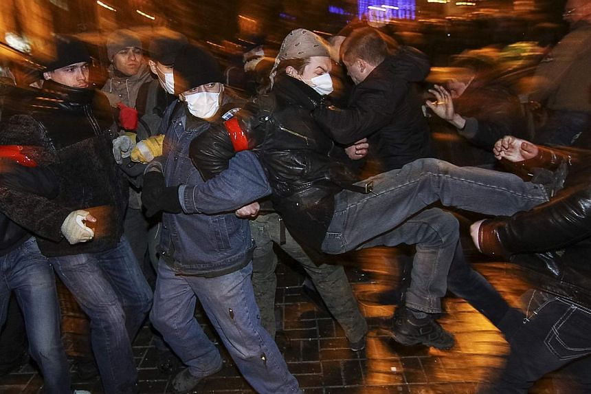 """Participants of an anti-war rally (left) clash with a pro-Russian supporters during their respective rallies in Donetsk March 13, 2014.Tatar community leader Mustafa Dzhemilev on Thursday urged Nato to intervene in Crimea to avert a """"massacre"""""""