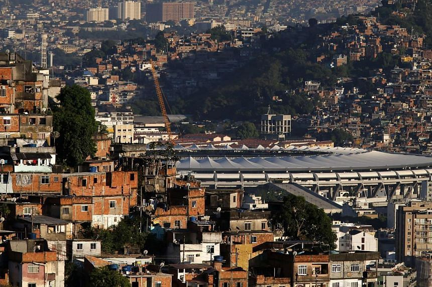 The Maracana stadium is seen between Turano slum (left) and Mangueira slum, which will be one of the stadiums hosting the 2014 World Cup soccer matches, in Rio de Janeiro March 11, 2014.-- PHOTO:REUTERS