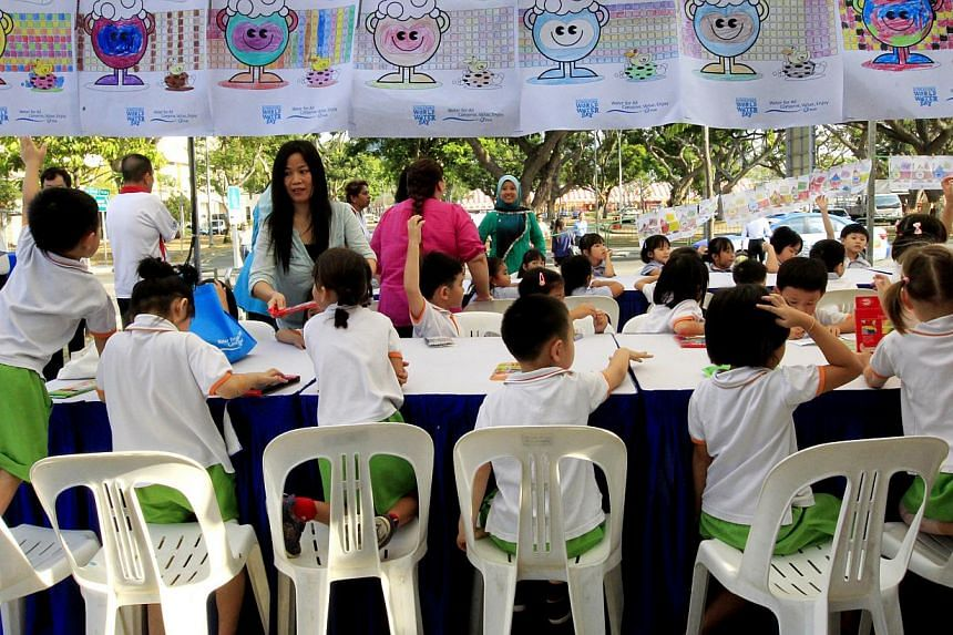 Pre-school children trying their hand at drawing PUB's mascot, Water Wally, on Wednesday at Haig Road Market and Food Centre as part of the national water agency's events to promote water conservation. -- ST PHOTO: CHEW SENG KIM