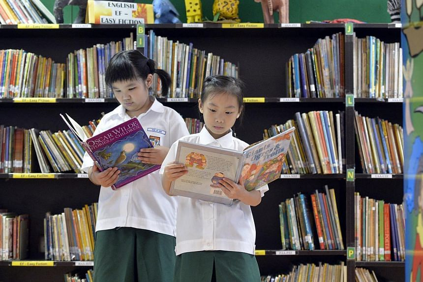 Primary 1 pupils Tan Si Min (left) and Freyann Lee En Qi at Corporation Primary's library. Having the books in the digital format means several pupils can read the same book at the same time.
